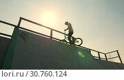 Купить «A professional BMX rider in grey hoodie going up on the ramp and standing on the top with his bike», видеоролик № 30760124, снято 20 июня 2019 г. (c) Константин Шишкин / Фотобанк Лори