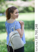 Купить «Rear view at pleasured woman walking in summer park, beige backpack hanging on shoulder», фото № 30760248, снято 3 июня 2018 г. (c) Кекяляйнен Андрей / Фотобанк Лори