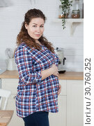 Купить «Портрет беременной женщины, держащей живот и стоящей в кухне», фото № 30760252, снято 17 февраля 2019 г. (c) Кекяляйнен Андрей / Фотобанк Лори