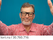Купить «Happy positive man pensioner wearing red shirt and stylish eyeglasses», фото № 30760716, снято 10 марта 2019 г. (c) Pavel Biryukov / Фотобанк Лори