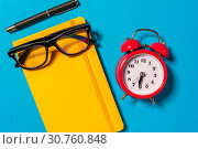 Купить «Alarm clock, empty notebook on blue background.», фото № 30760848, снято 22 мая 2019 г. (c) Pavel Biryukov / Фотобанк Лори