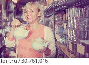 Купить «woman choosing clay kettle», фото № 30761016, снято 29 ноября 2017 г. (c) Яков Филимонов / Фотобанк Лори
