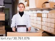 Купить «Female worker transporting cart cardboard cases», фото № 30761076, снято 22 апреля 2017 г. (c) Яков Филимонов / Фотобанк Лори