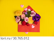 Opened red envelope with flowers arrangements on yellow background, top view. Festive greeting concept. Стоковое фото, фотограф YAY Micro / easy Fotostock / Фотобанк Лори