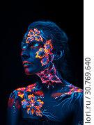 Купить «Beautiful flowers in UV light on a young girl face and body», фото № 30769640, снято 5 апреля 2019 г. (c) Sergii Zarev / Фотобанк Лори