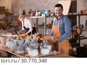 man and woman potters holding ceramic vessels in atelier. Стоковое фото, фотограф Яков Филимонов / Фотобанк Лори