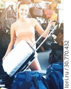 Купить «Redhead teenager girl choosing new large plastic luggage bag», фото № 30770432, снято 15 сентября 2016 г. (c) Яков Филимонов / Фотобанк Лори