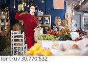 Купить «Buyer looks at the artichokes», фото № 30770532, снято 1 марта 2017 г. (c) Яков Филимонов / Фотобанк Лори