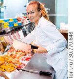 Купить «Female seller wearing uniform working with fresh meat», фото № 30770648, снято 23 февраля 2020 г. (c) Яков Филимонов / Фотобанк Лори