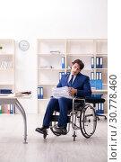 Купить «Young male employee in wheelchair working in the office», фото № 30778460, снято 8 января 2019 г. (c) Elnur / Фотобанк Лори