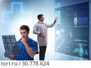 Купить «Doctor in telemedicine concept looking at x-ray image», фото № 30778624, снято 22 мая 2019 г. (c) Elnur / Фотобанк Лори