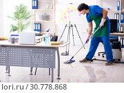 Купить «Male handsome professional cleaner working in the office», фото № 30778868, снято 7 января 2019 г. (c) Elnur / Фотобанк Лори