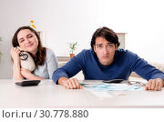 Купить «Young couple in budget planning concept», фото № 30778880, снято 22 января 2019 г. (c) Elnur / Фотобанк Лори