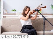 Купить «Female beautiful musician playing violin at home», фото № 30779016, снято 1 октября 2018 г. (c) Elnur / Фотобанк Лори