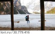 Купить «Young woman standing on a lago di braies frozen coast with a big backpack», видеоролик № 30779416, снято 20 мая 2019 г. (c) Константин Шишкин / Фотобанк Лори