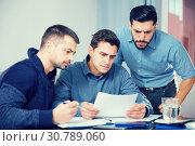 Купить «Three troubled men discussing documents at desk», фото № 30789060, снято 10 января 2018 г. (c) Яков Филимонов / Фотобанк Лори