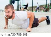 Купить «man performs push-ups on sportsground», фото № 30789108, снято 25 ноября 2017 г. (c) Яков Филимонов / Фотобанк Лори