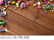 Купить «chocolate eggs and candy drops on wooden table», фото № 30790308, снято 22 марта 2018 г. (c) Syda Productions / Фотобанк Лори