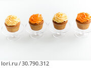 Купить «cupcakes with frosting on confectionery stands», фото № 30790312, снято 6 июля 2018 г. (c) Syda Productions / Фотобанк Лори