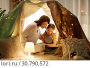 Купить «happy family reading book in kids tent at home», фото № 30790572, снято 27 января 2018 г. (c) Syda Productions / Фотобанк Лори