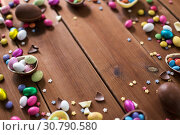 Купить «chocolate eggs and candy drops on wooden table», фото № 30790580, снято 22 марта 2018 г. (c) Syda Productions / Фотобанк Лори
