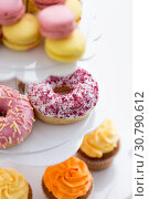 Купить «close up of glazed donuts and cupcakes on stand», фото № 30790612, снято 6 июля 2018 г. (c) Syda Productions / Фотобанк Лори