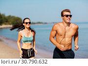 Купить «couple with earphones running along on beach», фото № 30790632, снято 1 августа 2018 г. (c) Syda Productions / Фотобанк Лори