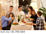 Купить «happy family having dinner party at home», фото № 30790684, снято 15 декабря 2018 г. (c) Syda Productions / Фотобанк Лори