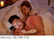 Купить «man using smartphone while girlfriend is sleeping», фото № 30790712, снято 5 января 2019 г. (c) Syda Productions / Фотобанк Лори