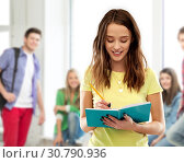 teenage student girl writing to diary or notebook. Стоковое фото, фотограф Syda Productions / Фотобанк Лори