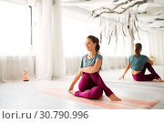 Купить «woman doing yoga exercise at studio», фото № 30790996, снято 21 июня 2018 г. (c) Syda Productions / Фотобанк Лори
