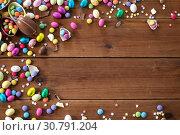 Купить «chocolate eggs and candy drops on wooden table», фото № 30791204, снято 22 марта 2018 г. (c) Syda Productions / Фотобанк Лори