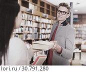 Купить «Adult guy helping young female student», фото № 30791280, снято 18 января 2018 г. (c) Яков Филимонов / Фотобанк Лори