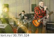 Купить «Bearded guy soloist playing guitar in studio», фото № 30791324, снято 26 октября 2018 г. (c) Яков Филимонов / Фотобанк Лори