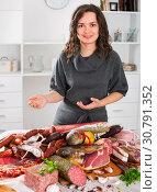 Купить «Woman costs near table on which sausages and smoked meat», фото № 30791352, снято 3 апреля 2020 г. (c) Яков Филимонов / Фотобанк Лори