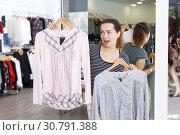 Купить «Woman holding and showing blouse on hanger», фото № 30791388, снято 10 октября 2018 г. (c) Яков Филимонов / Фотобанк Лори