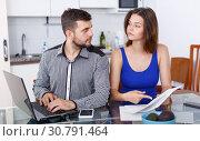 Купить «Serious young man and woman with financial documents near laptop», фото № 30791464, снято 6 июля 2018 г. (c) Яков Филимонов / Фотобанк Лори