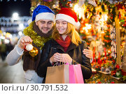 Купить «Girl with boy in Christmas hat choosing decorations», фото № 30791532, снято 14 декабря 2017 г. (c) Яков Филимонов / Фотобанк Лори