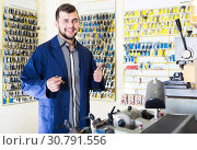 Купить «positive man worker displaying result of his key making in workshop», фото № 30791556, снято 5 апреля 2017 г. (c) Яков Филимонов / Фотобанк Лори