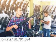 Купить «Friends choosing air-powered gun», фото № 30791584, снято 4 июля 2017 г. (c) Яков Филимонов / Фотобанк Лори