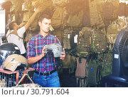 Купить «Young guys choosing helmet in military shop», фото № 30791604, снято 4 июля 2017 г. (c) Яков Филимонов / Фотобанк Лори