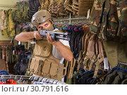 Купить «man in army uniform with weapon in military market», фото № 30791616, снято 4 июля 2017 г. (c) Яков Филимонов / Фотобанк Лори