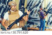 Купить «Young guys in military equipment with rifle in airsoft shop», фото № 30791620, снято 4 июля 2017 г. (c) Яков Филимонов / Фотобанк Лори