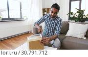 Купить «male video blogger opening parcel box at home», видеоролик № 30791712, снято 26 апреля 2019 г. (c) Syda Productions / Фотобанк Лори