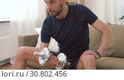 Купить «man exercising with dumbbells at home», видеоролик № 30802456, снято 15 мая 2019 г. (c) Syda Productions / Фотобанк Лори
