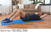 Купить «man making abdominal exercises at home», видеоролик № 30802500, снято 15 мая 2019 г. (c) Syda Productions / Фотобанк Лори