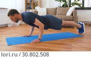 Купить «man doing push ups at home», видеоролик № 30802508, снято 15 мая 2019 г. (c) Syda Productions / Фотобанк Лори