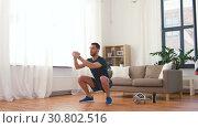 Купить «man exercising and doing squats at home», видеоролик № 30802516, снято 15 мая 2019 г. (c) Syda Productions / Фотобанк Лори