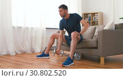 Купить «man exercising with dumbbells at home», видеоролик № 30802520, снято 15 мая 2019 г. (c) Syda Productions / Фотобанк Лори