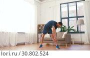 Купить «man exercising and leaning at home», видеоролик № 30802524, снято 15 мая 2019 г. (c) Syda Productions / Фотобанк Лори